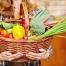 Hände einer Frau tragen Einkaufskorb voller Gemüse im Supermarkt