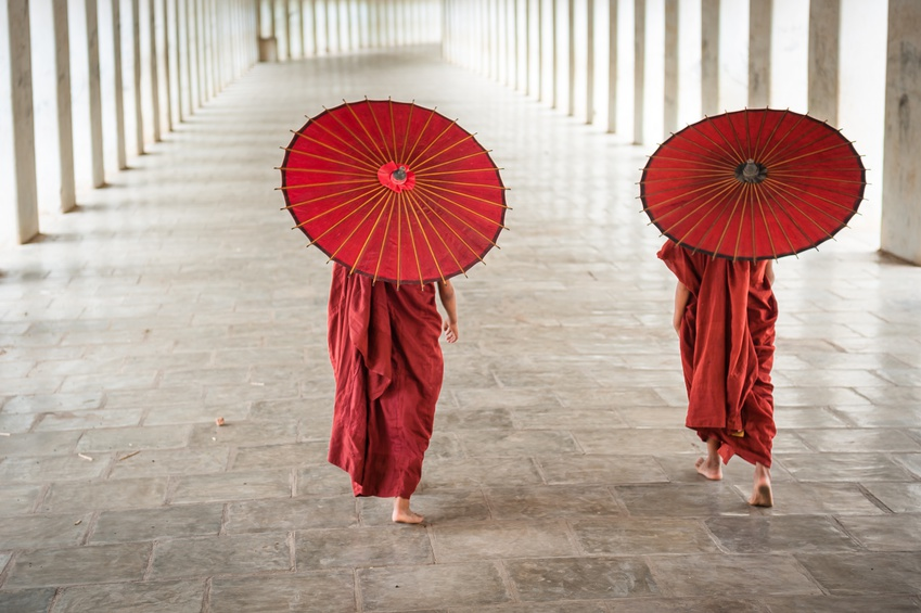 Two young buddhist monk are walking in temple. They have characteristic red dress and parasol