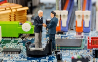 Zwei Manager auf Computerplatine, Symbolfoto für Computer, Anschaffung, Partnerschaft, B2B