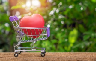 Red Heart Shape On Mini Shopping Cart Over Nature Background